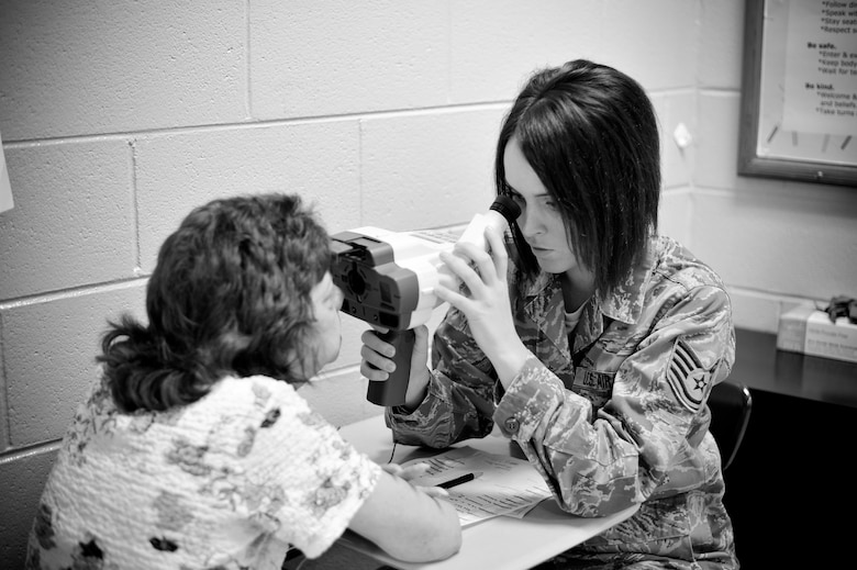 """Tech Sgt. Kaitlyn Conner, a laboratory technician with the 180th Fighter Wing, Ohio Air National Guard, conducts a vision test July 15, 2013, at Martin Middle School in Martin, Tenn. Conner and about 130 service members from the Air National Guard, Naval Reserves and the Army came together in the West Tenn. Community to provide free medical care as part of Innovative Readiness Training in support of the two-week """"Hope of Martin"""" health fair. As of July 15, the medical team had provided over 700 pairs of glasses to members of the Martin and surrounding communities. Air National Guard photo by Master Sgt. Beth Holliker (Released)."""