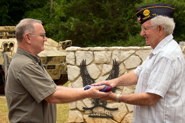 Master Sgt. Jeff Walston, a public affairs technician assigned to the 307th Bomb Wing at Barksdale Air Force Base La., presents a tattered U.S. flag to Bill Walston, 1st Vice Commander, American Legion Post 418, at the American Legion post in Troup, Texas, July 4, 2013. Sergeant Walston received the flag from one of the managers of the Silver Star Restaurant in Bossier City, La., after he noticed the flag was damaged. The American Legion post in Troup accepts flags to be retired from individuals and organizations, and once or twice a year retires them with the assistance of a local Boy Scout Troop. (Courtesy photo by Eva Klimentova)