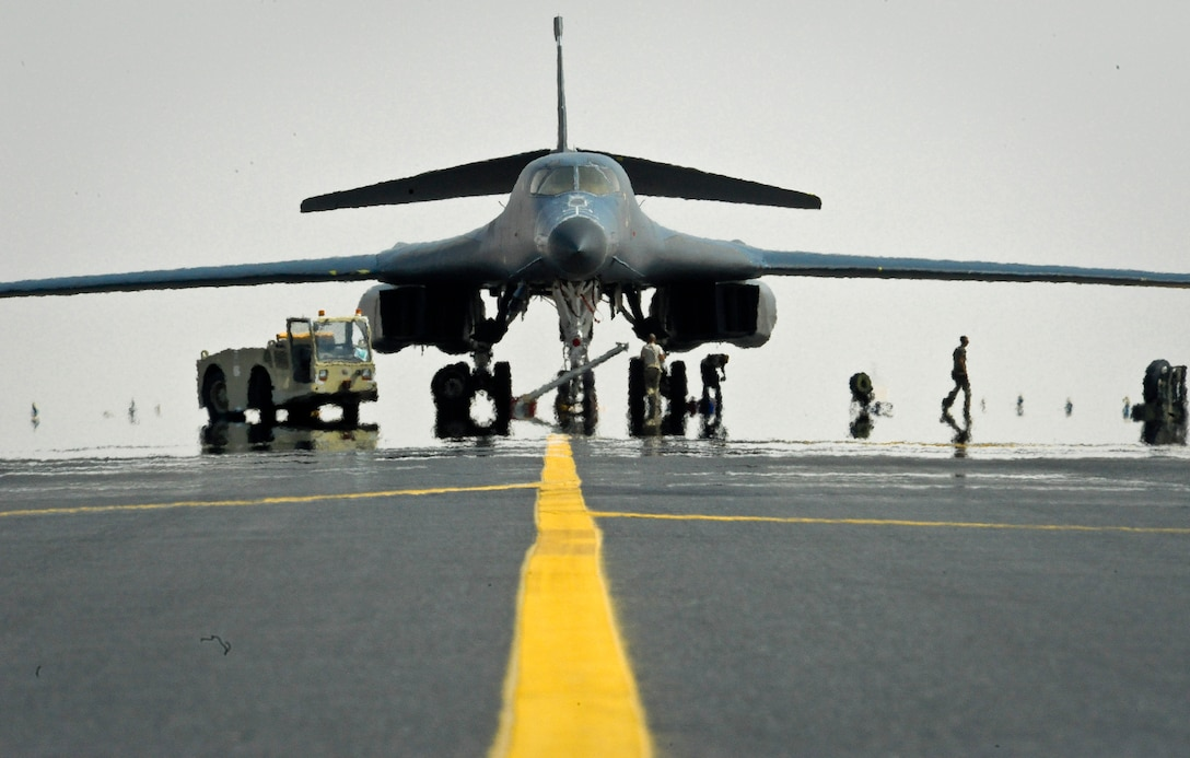 B-1B Lancer crew chiefs from the 34th Aircraft Maintenance Unit work to fix a blown tire as the sun heats up the tarmac at the 379th Air Expeditionary Wing in Southwest Asia, July 15, 2013. As these crew chiefs repair the blown tire, 379th Expeditionary Maintenance Group B-1 quality assurance inspector, Staff Sgt. Daniel Sanney, ensures the work is completed following safety guidelines. Sanney and these crew chiefs are deployed from Ellsworth Air Force Base, S.D. (U.S. Air Force photo/Senior Airman Benjamin Stratton)