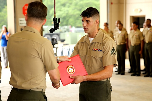 Cpl. Lucas Matte, a motor transport technician with Marine Wing Support Squadron 273, is presented an award from Col. William Lieblein, the commanding officer of Marine Aircraft Group 31, during an awards ceremony, July 12, recognizing Matte for his superior performance throughout 2012. Matte was recognized by the Marine Corps Motor Transport as the Motor Transport Technician of the Year for 2012, an award earned by Matte after being selected from a occupational field that contains almost 15,000 Marines.