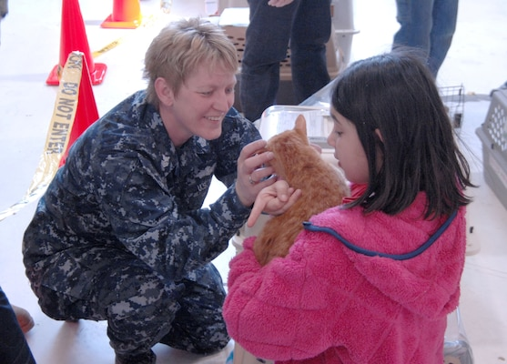 Petty Officer 1st Class Laurie Roods, Navy Operational Support Center Denver, helps Gloria Loveday find her cat after landing at Denver International Airport March 24. Members of all four military branches are working in support of the aerial port of debarkation at DIA as part of Operation Pacific Passage. DIA began receiving military dependents March 24, joining Seattle-Tacoma International Airport, Wash., and Travis Air Force Base, Calif. as points of debarkation for military dependents leaving Japan following the March 11 earthquake and tsunami.