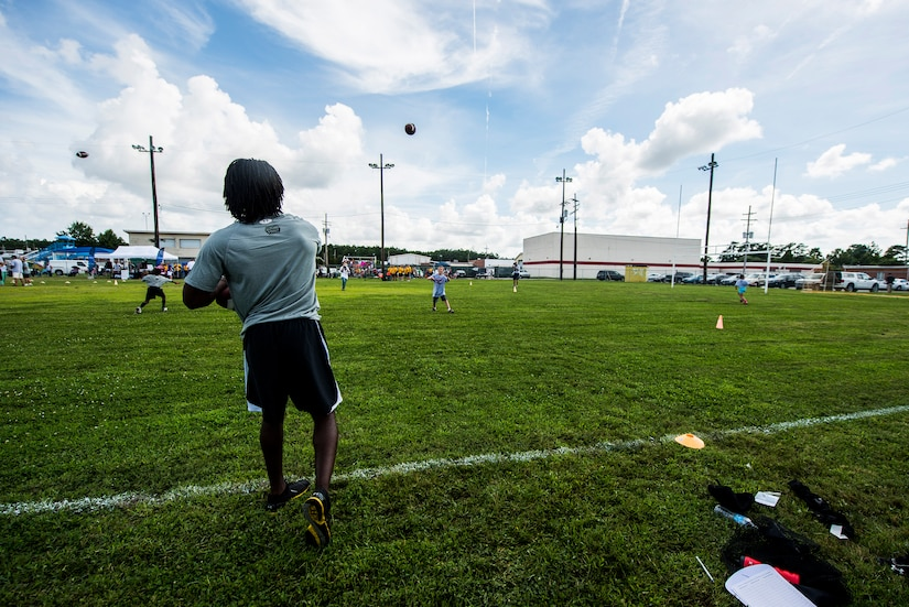 Andre Roberts, Arizona Cardinals wide receiver, throws the ball to a child during the Andre Roberts Pro Camp, July 15, 2013, at Joint Base Charleston - Weapons Station, S.C. More than 100 base children attended the Andre Roberts Pro Camp on July 15-16. The camp was paid for by Roberts, enabling the children to attend for free. (U.S. Air Force photo/ Senior Airman George Goslin)