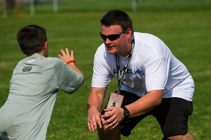 Jeff Cousins, West Ashley High School football coach, demonstrates how to block during the Andre Roberts Pro Camp, July 15, 2013, at Joint Base Charleston - Weapons Station, S.C. More than 100 base children attended the Andre Roberts Pro Camp on July 15-16. The camp was paid for by Roberts, enabling the children to attend for free. (U.S. Air Force photo/ Senior Airman George Goslin)