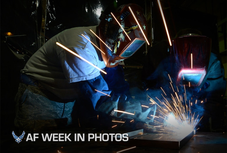 Senior Airman Kyle Zastrow performs an elbow weld while Senior Airman Isa Holland observes his work July 12, 2013, in Southwest Asia. Zastrow is using a metal inert gas welder and being trained on welding, which is not typical work for his career field. Holland is his trainer and will provide guidance on several aspects of his job during their deployment. Both are members of the combat metals shop, which uses two different career fields for a broader capability. Zastrow and Holland are deployed to the 386th Expeditionary Maintenance Squadron. (U.S. Air Force photo/Master Sgt. Christopher A. Campbell)