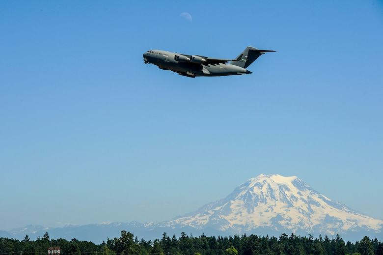 "A C-17 Globemaster III ascends over Joint Base Lewis-McChord, Wash., as Mount Rainier towers in the distance July 15, 2013. The C-17 piloted by Col. Wyn Elder, was performing a touch-and-go prior to its final approach during the colonel's ""fini flight"". Elder was the commander of the 62nd Airlift Wing. (U.S. Air Force photo/Tech. Sgt.  Sean Tobin)"