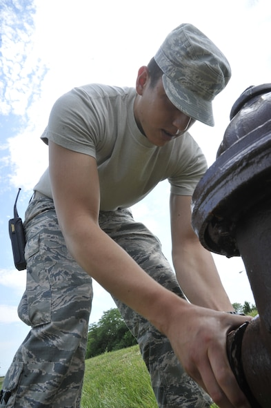 Airman 1st Class Edward Miramontes, 509th Civil Engineer Squadron water fuels maintenance journeyman, performs a hydrant flow test at Whiteman Air Force Base, Mo., June 9, 2013. This test is used to verify adequate supply pressure while under full pressure. If there is a break in the lines, water flow will  hinder the Whiteman mission. (U.S. Air Force photo by Airman 1st Class Keenan Berry/Released)
