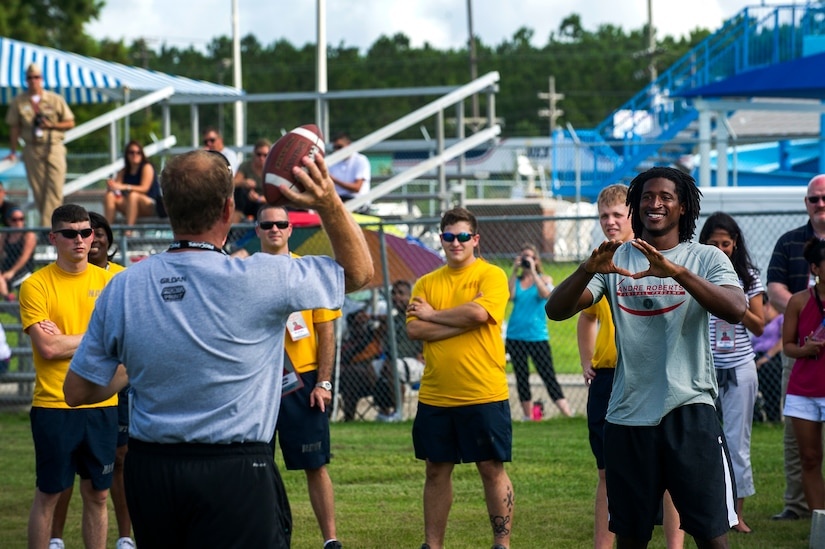 Jim Stoll, Pro Camps organizer, throws a ball to Andre Roberts, Arizona Cardinals wide receiver, to demonstrate proper receiving technique during the Andre Roberts Pro Camp, July 15, 2013, at Joint Base Charleston - Weapons Station, S.C. More than 100 base children attended the Andre Roberts Pro Camp on July 15-16. The camp was paid for by Roberts, enabling the children to attend for free. (U.S. Air Force photo/ Senior Airman George Goslin)