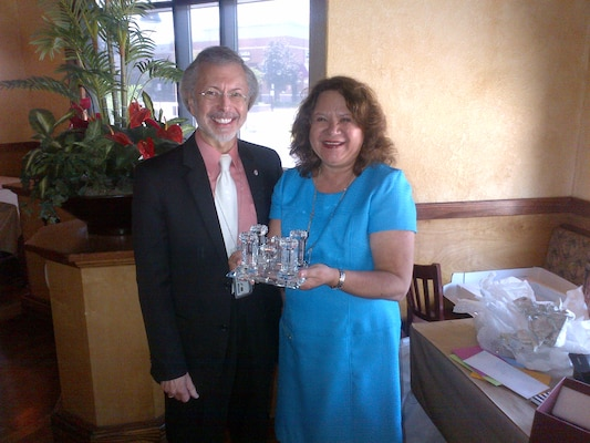 Lillian Almodovar receives commemorative Corps Castle from IWR Director Bob Pietrowsky at a ceremony celebrating her retirement.