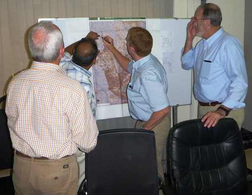 U.S. Army Corps of Engineers debris subject matter experts identify potential temporary sorting sites on a map with a Dhaka City Corporation engineer
