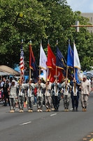 Guam native Sergeant Albert Opena III (carrying the Marine Corps flag in the center) and Texas native Corporal German Trevizo (far right) participate in the joint color guard as they march down Marine Corps Drive during the Liberation Day Parade July 21 on Guam. The annual parade concludes a series of memorials and celebrations around the island to honor local Chamorros and Marines who died at Japanese hands in the 1941 invasion and occupation and 1944 liberation of the island and celebrate the freedom of Guam.  Local villages and organizations hosted the Guam Marines on various floats in the parade in appreciation for the Marines who liberated the island from Japanese occupation in 1944.    (Official U.S. Marine Corps photo by Sgt. John Raufmann)
