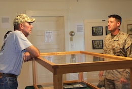 Jon Hemp, the co-founder of The Dawgs Project, speaks to Lt. Col. Kevin Prindiville, the provost marshal with the Camp Pendleton Marine Corps Police Department, during the sneak preview of the Dawgs of War exhibit at the Ranch House here July 20. service members, families and friends joined together at the exhibit before unveiling a sign at the Provost Marshals kennels.