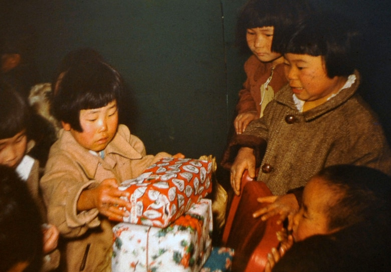 South Korean orphans open presents donated by retired U.S. Army Maj. E. Vernon Smith Jr. and his family. Smith used photography as a way to preserve memories of his experience during his rotation there from 1956-58. (Courtesy photo/Released)