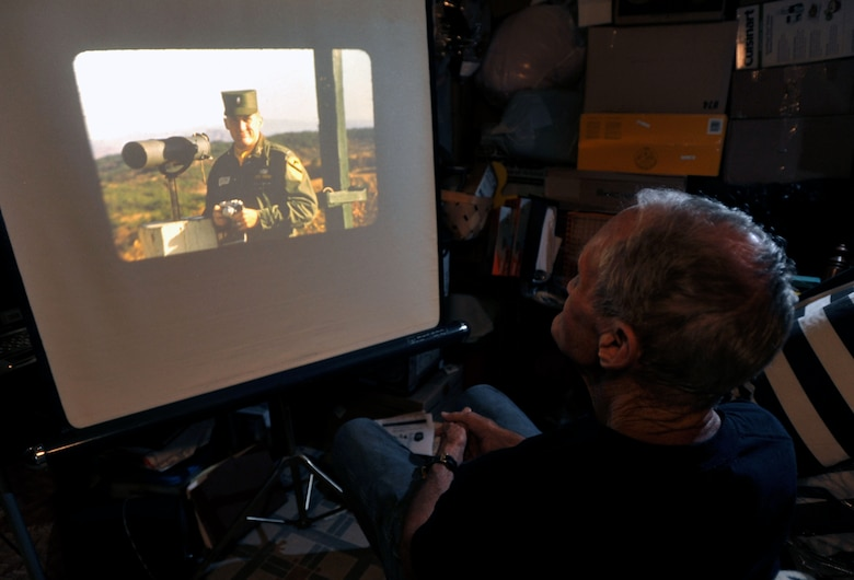 Retired U.S. Army Maj. E. Vernon Smith Jr. looks at a photo of himself as a first lieutenant while stationed in South Korea at his home in central Virginia, July 20, 2013. In support of the Korean Armistice Agreement signed July 27, 1953, Smith was assigned as the executive officer of the 24th Infantry Division Replacement Company, which later became the 1st Cavalry Division, and oversaw the logistics of coordinating replacement units. (U.S. Air Force photo by Staff Sgt. Katie Gar Ward/Released)