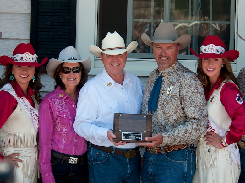 Air Force Chief of Staff Gen. Mark A. Welsh III receives a plaque from Cheyenne Frontier Days committee members, July 20, 2013, prior to the start of the 117th annual CFD parade as the general's wife, Betty; Chloe Pfoor, Miss Frontier; and Kaci Malmborg, her Lady-in-Waiting; look on. Welsh, who served as grand marshal for the opening parade, visited the region to participate in CFD events, but also to thank Airmen and the community for the continued service and support. (U.S. Air Force photo by R.J. Oriez)