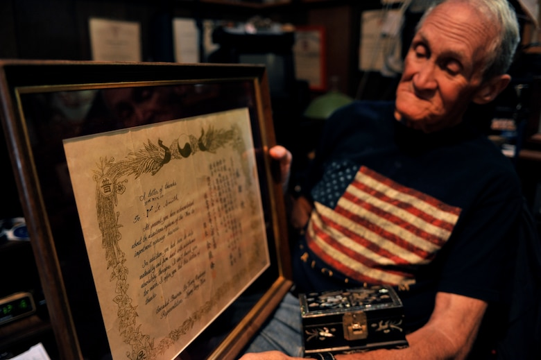 Retired U.S. Army Maj. E. Vernon Smith Jr. looks at a framed letter of appreciation from a South Korean orphanage while in his home in central Virginia, July 20, 2013. Smith donated clothes and toys to the orphanage while stationed near the Korean demilitarized zone in 1956, and said seeing the impoverished children made him feel compelled to help. (U.S Air Force photo by Staff Sgt. Katie Gar Ward/Released)