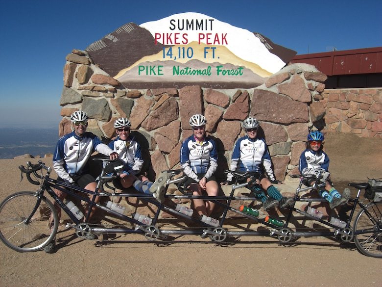 """PETERSON AIR FORCE BASE, Colo.—Lt. Col. James Lawrence, a pilot with the 200th Airlift Squadron Colorado Air National Guard, and his family take a well-deserved rest at the summit of Pikes Peak after pedaling their way up on the family's """"quint"""" bicycle. For the Lawrence family, riding bikes of all shapes and sizes has become a passion. (Courtesy photo)"""
