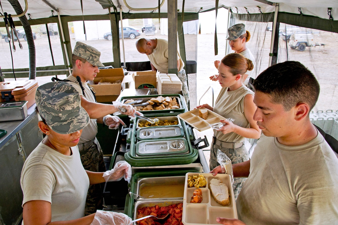 Airmen serve dinner in the field in a mobile kitchen trailer during Global Medic 13 on Fort McCoy, Wis., July 16, 2013. The food service specialists are assigned to the 940th Force Support Squadron, Beale Air Force Base, Calif.