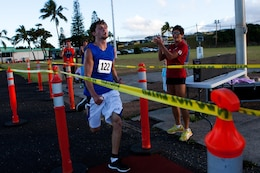"Dallas Giestige, an Ohio native in Oahu for vacation, crosses the finish line of the Camp Smith 5K Grueler first, with a time of 20 minutes, 47 seconds, here July 20. ""It was tough,"" said the cross-country athlete. ""I'm always looking forward to a challenge."""