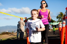 Lauren McMillen, a member of the Oahu community, crosses the finish line with her 7-year-old son, Liam, during the Camp Smith 5K Grueler here July 7.  The race, a part of the Commanding Officer's Fitness Series, was open to service members, their families and the general public.
