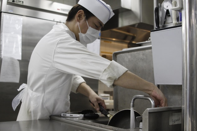 Yasunobu Asaeda, Club Iwakuni supervisor, washes a pan used to complete an order during a busy breakfast rush at Club Iwakuni at Marine Corps Air Station Iwakuni, Japan, July 20, 2013. When the number of people working is low, Asaeda steps in to take care of miscellaneous tasks, such as washing dishes.