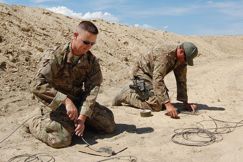 Colorado Air National Guard Tech. Sgt. Andrew LeBeau and Airman 1st Class Darrell Linkus, 140th Explosive Ordnance Disposal Flight, wrap detonation cord on cardboard for a diesel display charge during the EOD Demo Day July 12, 2013 at Airburst Range, Fort Carson, Colo. (U.S. Air National Guard photo by Capt. Kinder Blacke)