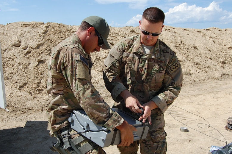 """Colorado Air National Guard Airman 1st Class Darrell Linkus and Tech. Sgt. Andrew LeBeau, 140th Explosive Ordnance Disposal Flight, work together to build a hydraulic explosive tool, or """"Bootbanger"""", during the EOD Demo Day July 12, 2013 at Airburst Range, Fort Carson, Colo. (U.S. Air National Guard photo by Capt. Kinder Blacke)"""