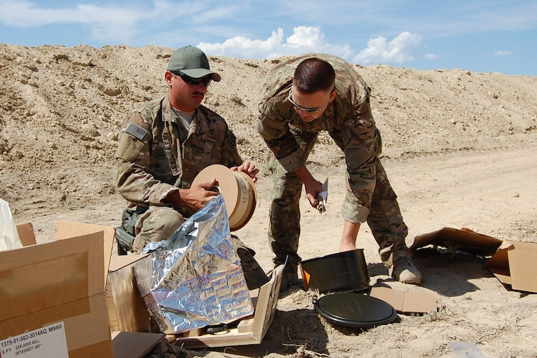 Colorado Air National Guard Airman 1st Class Darrell Linkus and Tech. Sgt. Andrew LeBeau, 140th Explosive Ordnance Disposal Flight,  construct explosive charges during the EOD Demo Day July 12, 2013 at Airburst Range, Fort Carson, Colo. (U.S. Air National Guard photo by Capt. Kinder Blacke)