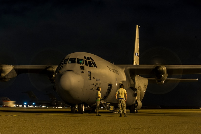 Members of the crew of a C-130J-30 from Dyess Air Force Base, Texas, wait outside of the aircraft before takeoff after an early morning cargo load July 23, 2013, at Joint Base Charleston - Air Base, S.C. The C-130J-30 was loaded with rations and supplies bound for Bogota. The C-130J-30 is a stretch version of the C-130J, a proven, highly reliable and affordable airlifter. The C-130J-30 adds 15 feet to the fuselage, increasing usable space in the cargo compartment. (U.S. Air Force photo/ Senior Airman George Goslin)