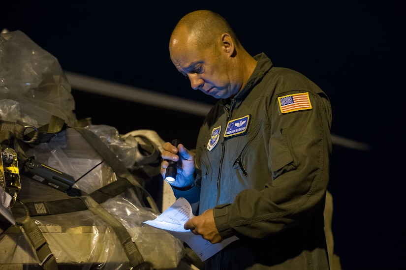 Chief Master Sgt. Jack McCracken, 40th Airlift Squadron loadmaster with the 317th Airlift Group from Dyess Air Force Base, Texas, reviews logs after loading cargo onboard a C-130 during an early morning cargo load July 23, 2013, at Joint Base Charleston - Air Base, S.C. The C-130 was loaded with rations and  supplies bound for Bogota. The C-130J-30 is a stretch version of the C-130J, a proven, highly reliable and affordable airlifter. The C-130J-30 adds 15 feet to the fuselage, increasing usable space in the cargo compartment. (U.S. Air Force photo/ Senior Airman George Goslin)