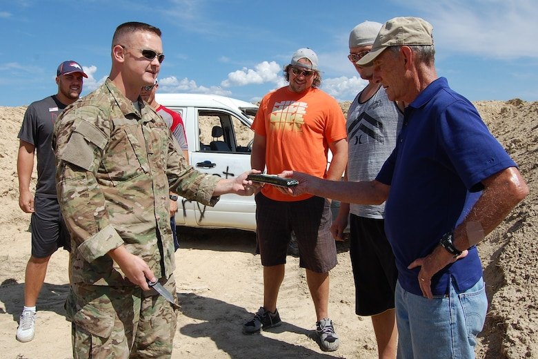 Colorado Air National Guard Tech. Sgt. Andrew LeBeau, 140th Explosive Ordnance Disposal Flight, shows Col. (ret) Hugh Garland a block of C4, a highly explosive material, during the EOD Demo Day July 12, 2013 at Airburst Range, Fort Carson, Colo. (U.S. Air National Guard photo by Capt. Kinder Blacke)