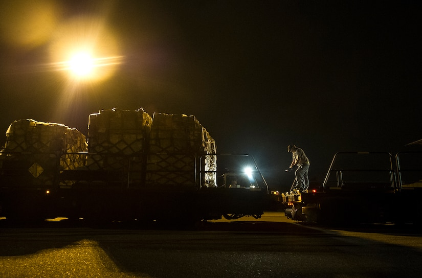 A civilian with the 437th Aerial Port Squadron directs a K-loader during an early morning cargo load July 23, 2013, at Joint Base Charleston - Air Base, S.C. The C-130J-30 was loaded with rations and supplies bound for Bogota. The C-130J-30 is a stretch version of the C-130J, a proven, highly reliable and affordable airlifter. The C-130J-30 adds 15 feet to the fuselage, increasing usable space in the cargo compartment. (U.S. Air Force photo/ Senior Airman George Goslin)