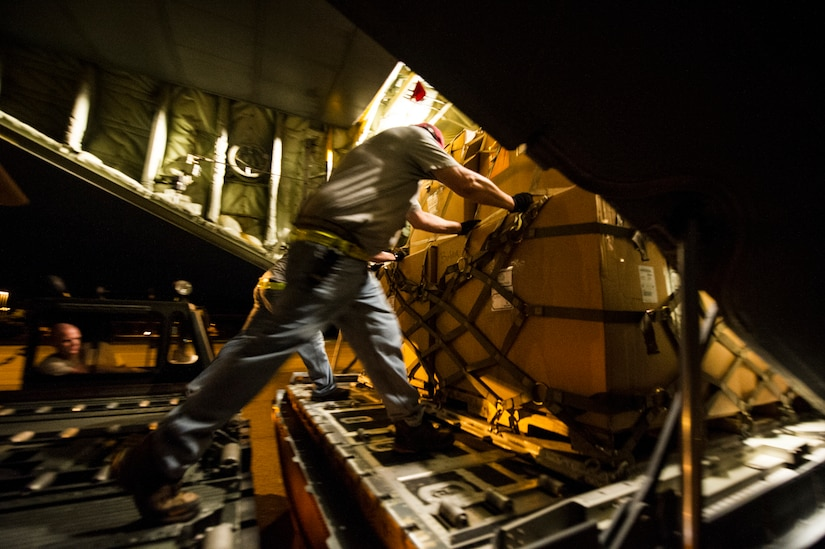 Civilians from the 437th Aerial Port Squadron push cargo onto a C-130J-30 from Dyess Air Force Base, Texas, during an early morning cargo load July 23, 2013, at Joint Base Charleston - Air Base, S.C. The C-130J-30 was loaded with rations and supplies bound for Bogota. The C-130J-30 is a stretch version of the C-130J, a proven, highly reliable and affordable airlifter. The C-130J-30 adds 15 feet to the fuselage, increasing usable space in the cargo compartment. (U.S. Air Force photo/ Senior Airman George Goslin)