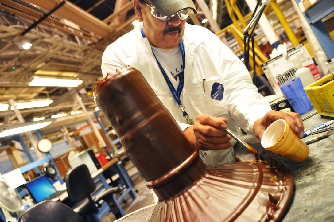 Electroplater Alfonso Tijerina applies small amounts of wax to an F100 drive shaft. Attention to detail is required because every piece of the engine part that is not going to be plated must be covered with protective wax. (Air Force photo by Micah Garbarino)