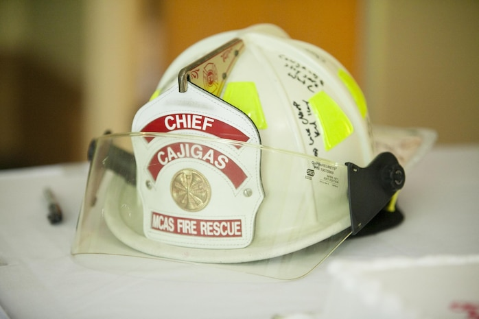Chief Hector Cajigas, Air Station fire chief, received a fireman helmet signed by friends and coworkers during his retirement ceremony at the Air Station Officers' Club July 18. Cajigas retired after 32 years of service as a firefighter aboard the Air Station and Marine Corps Recruit Depot Parris Island, public safety officer for Port Royal and Marine. Cajigas served 28 of the 32 years in Beaufort and has been hired as the next Beaufort County deputy sheriff.