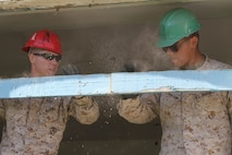 U.S. Marines Lance Cpl. Braxton R. Moody (left) and Private First Class Ismael Moctezumadelalanza with 9th Engineer Support Battalion works to clear debris from a window frame during renovation work on Erdmiin Oyun High School as part of Exercise Khaan Quest in the Nalaikh District of Ulaanbaatar, Mongolia, July 20, 2013. Khaan Quest is a regularly scheduled multinational exercise co sponsored this year by U.S. Marine Corps Forces, Pacific, and hosted annually by the Mongolian Armed Forces, designed to promote regional peace and security.
