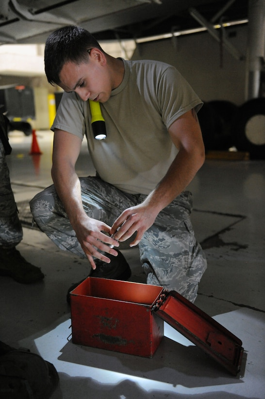 Airman 1st Class Daniel Villarreal, 393rd Aircraft Maintenance Unit load crew member, examines an impulse cartridge during a load crew competition at Whiteman Air Force Base, Mo., July 18, 2013. The Airmen were judged on dress and appearance, toolkit inspections, overall load time and a 25-question test. (U.S. Air Force photo by Airman 1st Class Shelby R. Orozco/Released)