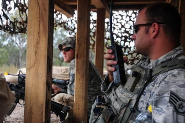 Staff Sgt. James Foster, 736th Security Forces Squadron combat arms noncommissioned officer in charge, checks the status of an entry control point at Williamson Airfield using radio communications July 22 during Talisman Saber 2013. The 736th SFS and 36th Mobility Response Squadron are part of the 36th Contingency Response Group, Andersen Air Force Base, Guam. The 36th CRG assumed command and control of the airfield from the 1st Battalion, 501st Parachute Infantry Regiment, 4th Brigade Combat Team, 25th Infantry Division (Airborne) and turned over command to the Royal Australian Air Force as part of a multiphase combined joint operation. Talisman Saber was designed to utilize a realistic scenario to train U.S. and Australian forces in planning and executing combined and joint military operations on land, air and sea. (U.S. Air Force photo by Airman 1st Class Marianique Santos/Released)