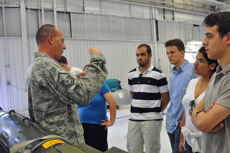 Graduate and doctoral engineering students from Brazil discuss the Joint Direct Attack Munition GBU-38 bomb with Master Sgt. Christopher Rasco, a load standardization team chief assigned to the 355th Maintenance Operations Squadron, at Davis-Monthan Air Force Base, July 24. The students were in Tucson, Ariz., visiting the nearby Raytheon Company as part of Brazil's Science Without Borders program and requested the opportunity to visit D-M.  The GBU-38 is the smallest version of the JDAM weighing in at approximately 500 pounds. (U.S. Air Force photo/Capt. Jonathan Simmons)
