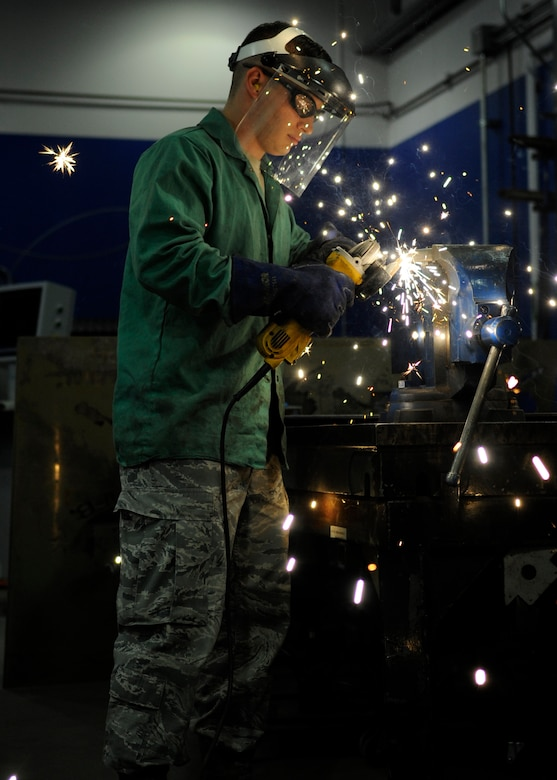 U.S. Air Force Senior Airman Robert Mason, 354th Maintenance Squadron metals technology journeyman, grinds a piece of titanium while fabricating a part for an F-16 Fighting Falcon at Eielson Air Force Base, Alaska, July 22, 2013. Metals tech Airmen use practically any metal to fabricate parts and tools for machinery base wide. (U.S. Air Force Senior Airman Shawn Nickel/Released)
