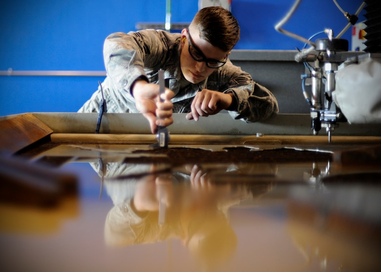U.S. Air Force Senior Airman Robert Mason, 354th Maintenance Squadron metals technology journeyman, uses a caliper to measure aluminum while fabricating a part for an F-16 Fighting Falcon at Eielson Air Force Base, Alaska, July 22, 2013. Commonly, a part for an aircraft can't be purchased or is just cheaper to produce. Metals tech Airmen can fabricate almost any part or tool from raw material. (U.S. Air Force Senior Airman Shawn Nickel/Released)