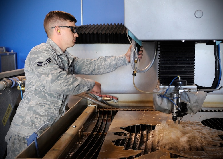 U.S. Air Force Senior Airman Robert Mason, 354th Maintenance Squadron metals technology journeyman, makes adjustments to a water jet while fabricating fuel caps for F-16 Fighting Falcons at Eielson Air Force Base, Alaska, July 22, 2013. Metals tech Airmen are certified to run the machine, which pierces metal with 55,000 pounds per square inch using water and an abrasive mixture. (U.S. Air Force Senior Airman Shawn Nickel/Released)