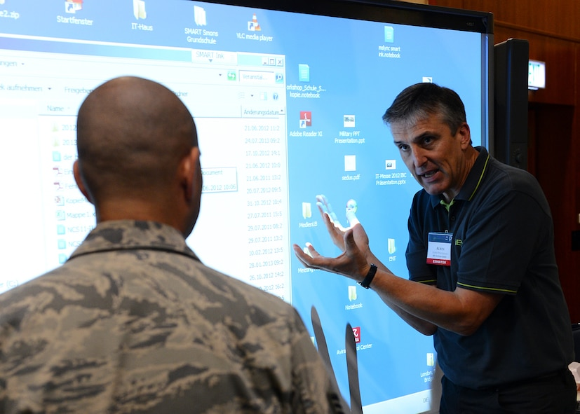 SPANGDAHLEM AIR BASE, Germany -- Alwin Puschmann, IBC Systems in Bitburg, explains how to operate an interactive whiteboard to U.S. Air Force Staff Sgt. Modesto Alcala, American Forces Network, at the 2013 Spangdahlem Technology Expo July 24, 2013. More than 25 exhibitors demonstrated their modern technology to the Spangdahlem community. The interactive whiteboard is intended for office or conference settings and uses multiple interface capabilities. (U.S. Air Force photo by Staff Sgt. Daryl Knee/Released)