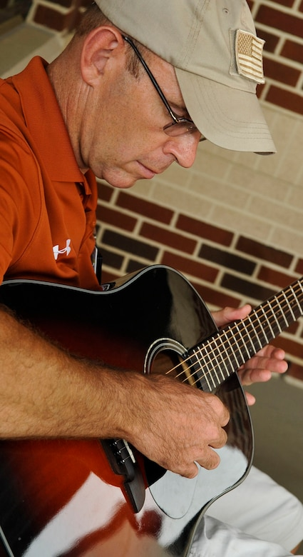 "Woody Groton, Fort Eustis Warrior Transition Unit site coordinator for the military adaptive sport program, plays his guitar during the ""Music for Morale"" program at Fort Eustis, Va., July 11, 2013. Groton started the program as a way to share his love for playing guitar while helping Soldiers in their recovery process. (U.S. Air Force photo by Staff Sgt. Wesley Farnsworth/Released)"
