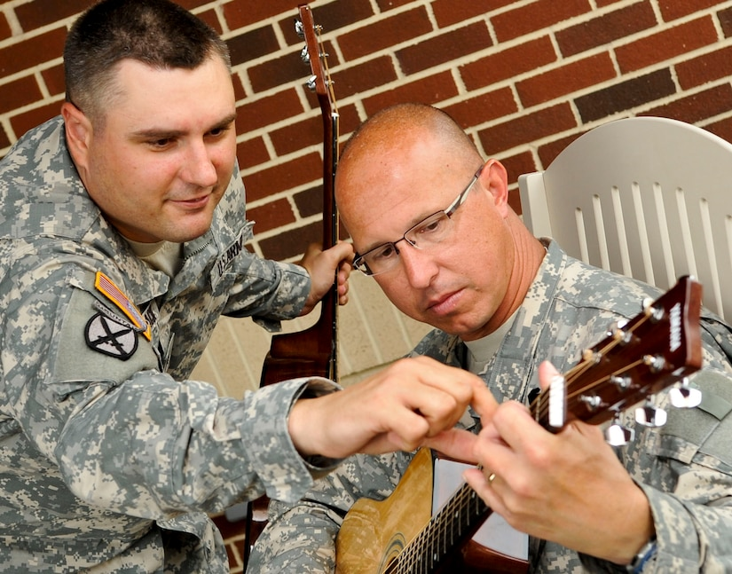 """(From left) U.S. Army Sgt. Scott Black instructs Lt. Col. Eric. Whitelock, fellow Warrior Transition Unit healing soldier, where to place his fingers on the guitar during the """"Music for Morale"""" program at Fort Eustis, Va., July 11, 2013. The program helps Soldiers improve memory while building camaraderie with fellow Soldiers. (U.S. Air Force photo by Staff Sgt. Wesley Farnsworth/Released)"""
