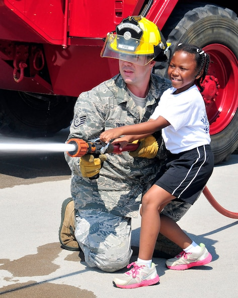 Staff Sgt. Zachary Troup, a firefighter with the 134th Air Refueling Wing Civil Engineering Squadron, helps a young member of the Knoxville Police Department Boot Camp Program man the firehose during a visit to McGhee Tyson ANG Base, Tennessee July 23.  The children participated in the program to learn opportunities that exist outside of thier local communities. (Air National Guard photo by Master Sgt. Kendra Owenby, 134 ARW Public Affairs)