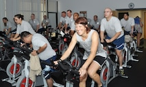 Marlyn Shults, 56th Aerospace Medicine Squadron exercise physiologist, participates in a spin class with Airmen July 17 at the 56th AMDS Health and Wellness Center. The class is part of the running clinic, a six-week-long program designed to improve fitness test scores. (U.S. Air Force photo/Staff Sgt. Luther Mitchell Jr.)