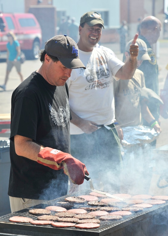 Members of the Great Falls Area Chamber of Commerce Military Affairs Committee cook the food served during the Montana Air National Guard Family Day picnic on Aug. 11, 2012. (U.S. Air Force photo/Staff Sgt. John Turner)