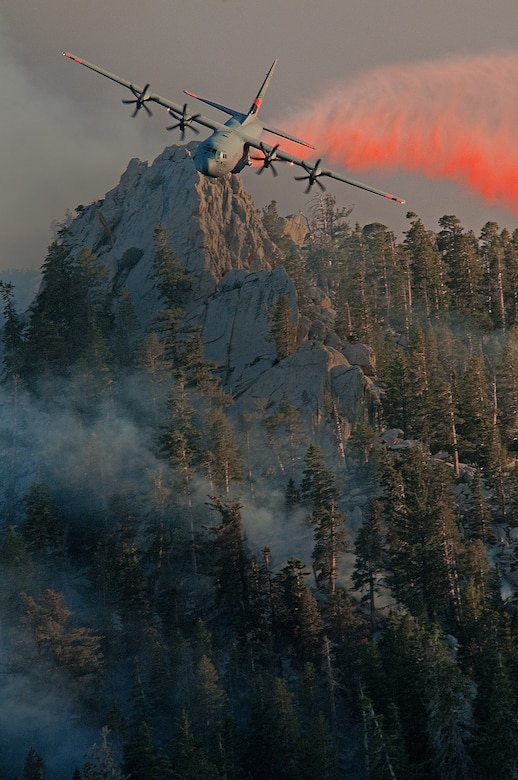 A C-130 Hercules aircraft releases fire retardant over the trees in the mountains above Palm Springs, Calif., July 19, 2013. The unit was activated to assist the community with wildfires. The C-130 Hercules is assigned to the 146th Airlift Wing, California Air National Guard. (U.S. Air National Guard photo/Senior Airman Nicholas Carzis)