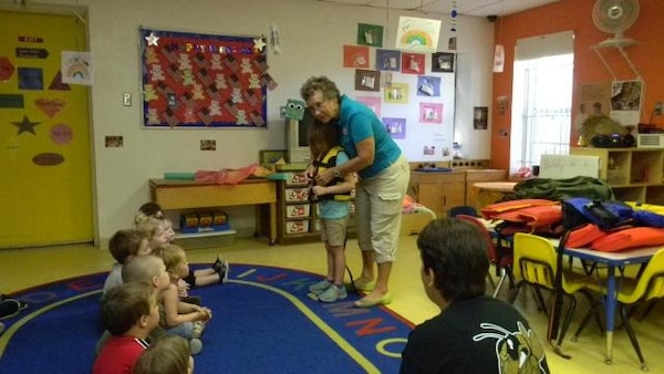 Water safety volunteer Pam VanderWeele shows a classroom of students the proper way to fit and fasten a life jacket.