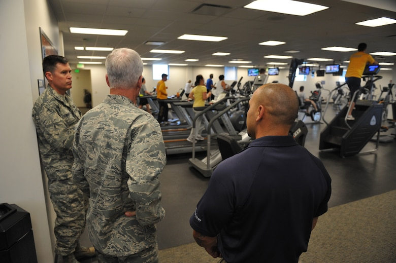 Bobby Padia, fitness center director, right, briefs, Gen. William Shelton, Air Force Space Command commander, and Col. Dan Wright, 460th Space Wing commander, during a tour of the facility July 23, on Buckley Air Force Base, Colo. The fitness center offers a variety of classes and programs to Airmen, their families and other eligible guests. (U.S. Air Force photo by Airman 1st Class Riley Johnson/Released)